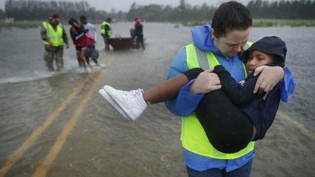 Mujer con niño en brazos en carretera inundada.
