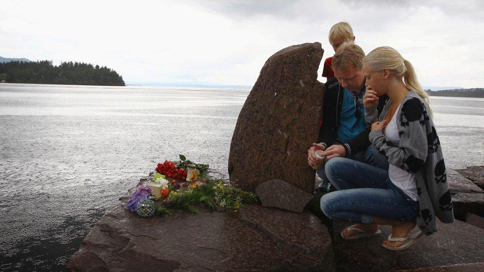 Personas rindiendo tributo a las víctimas cerca de la isla de Utøya.