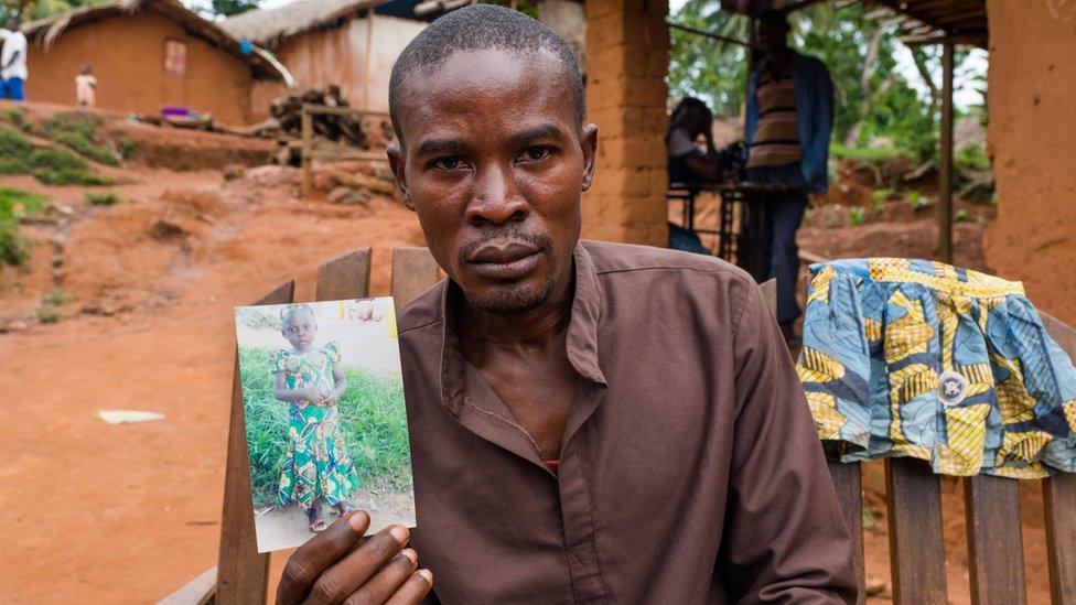 Abdula Libenge con una fotografía de su hija desaparecida.