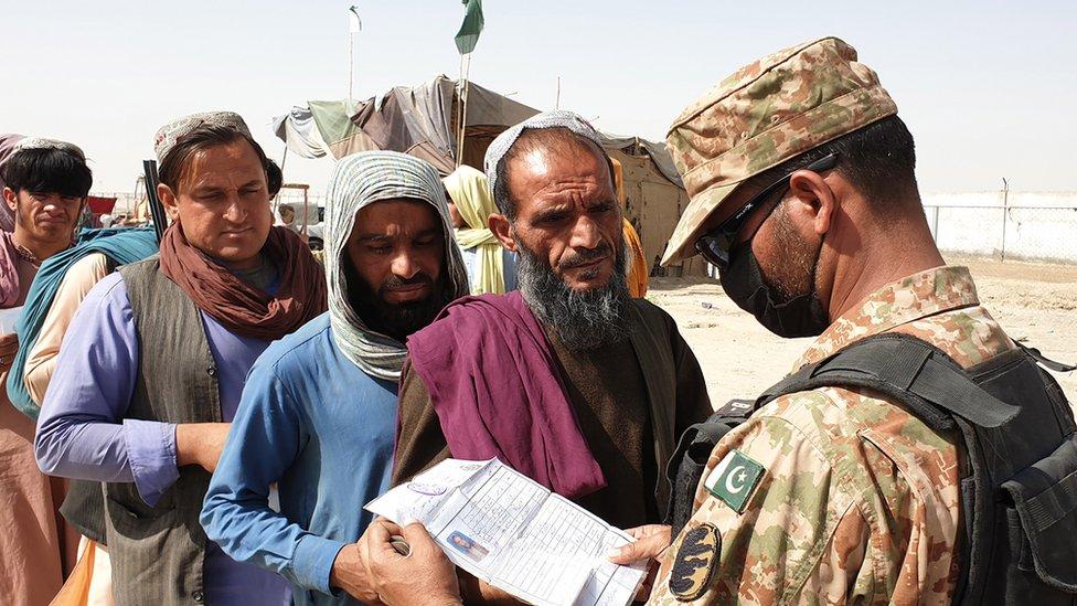 Soldado paquistaní examina los papeles de un migrante afgano