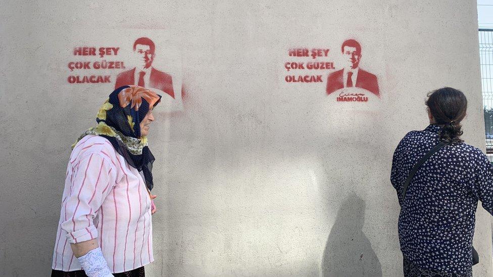 her şey çok güzel olacak duvar yazısı önünde iki kadın