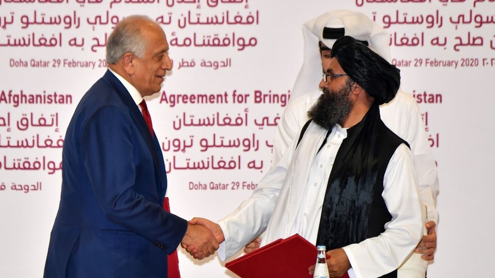 US Special Representative for Afghanistan Reconciliation Zalmay Khalilzad and Taliban co-founder Mullah Abdul Ghani Baradar shake hands after signing a peace agreement