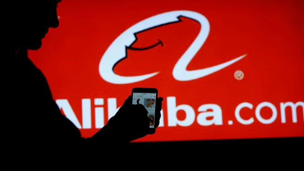 Hombre con la aplicación de Alibaba en el teléfono.