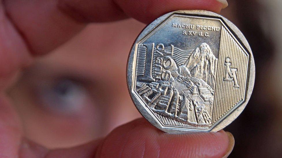 Persona con una moneda peruana en la mano