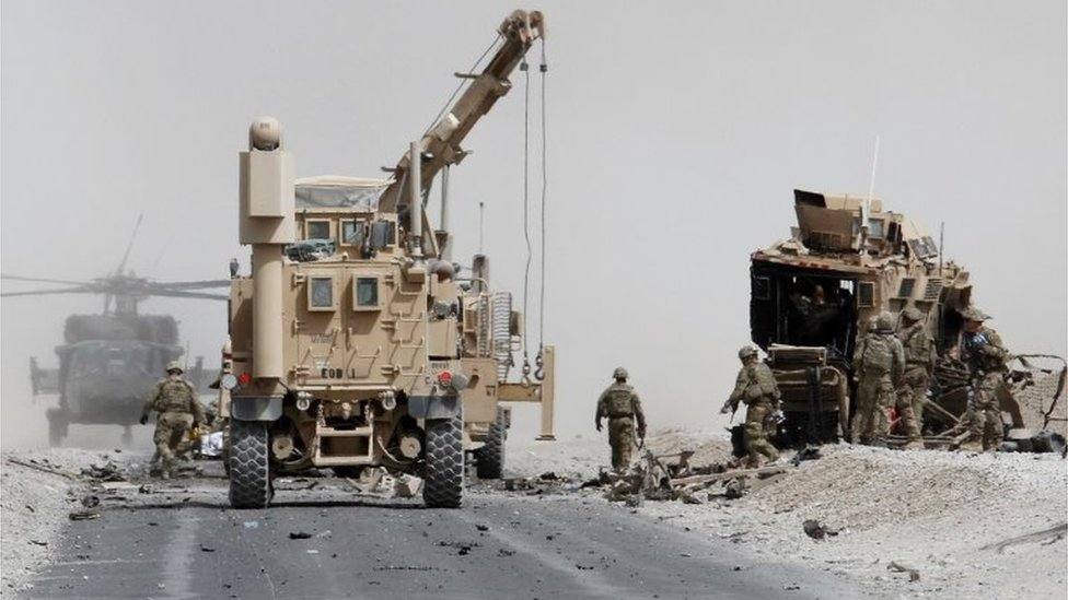 US troops assess the damage to an armoured vehicle of Nato-led military coalition after a suicide attack in Kandahar province, Afghanistan. Photo: August 2017