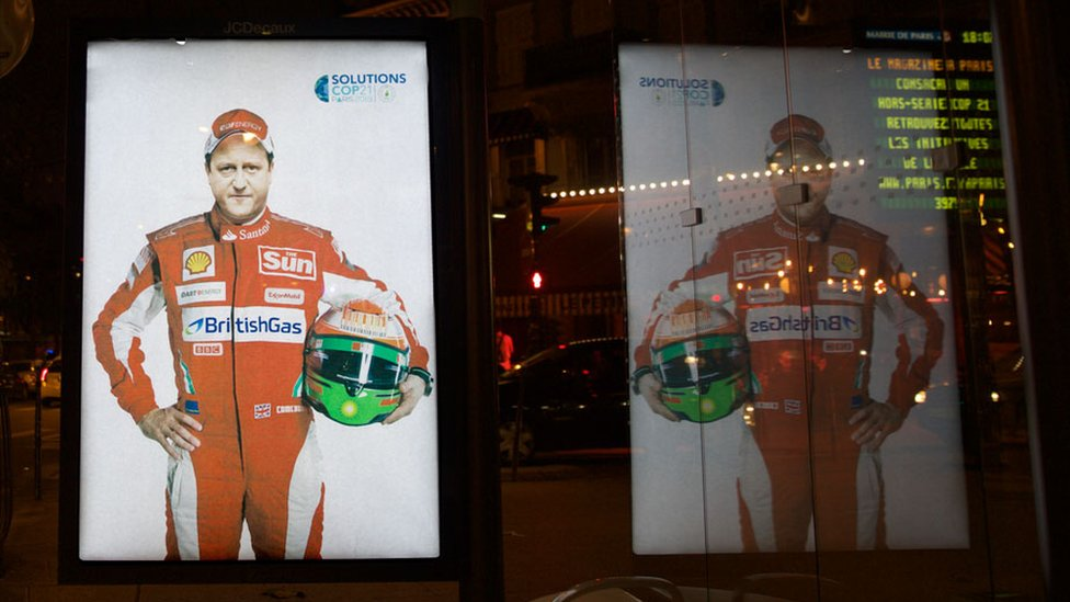 A poster featuring British Prime Minister David Cameron shows him in Formula 1 gear