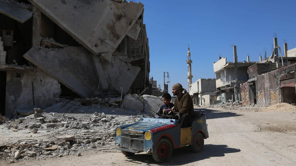 A Syrian man drives a home-made toy car through Beit Naim in the Eastern Ghouta on 7 March 2017