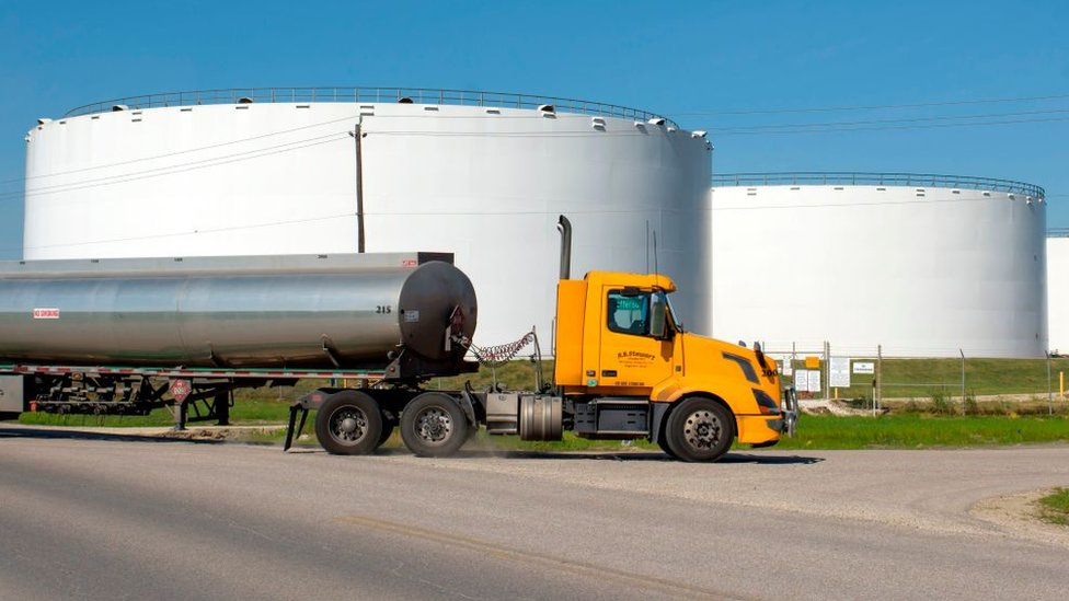 Camión en medio de tanques de almacenamiento