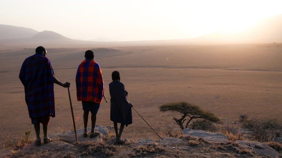 Maasai cattle herder, Parakapooni, and his brother and son look over the brown plains of the Serengeti, Tanzania.