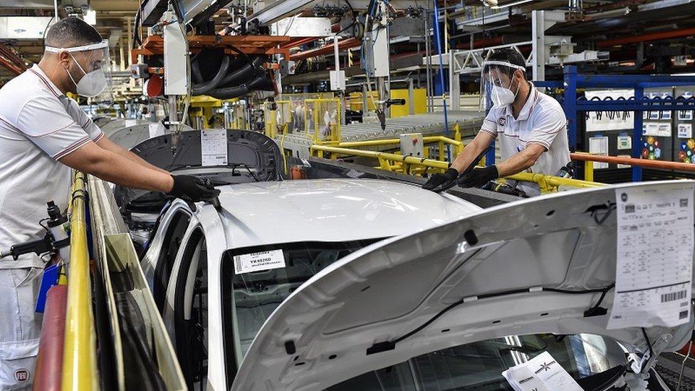 Dois homens trabalham em linha de montagem de carros
