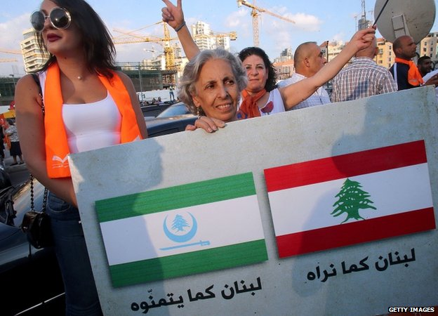 "Supporters of Lebanese Christian leader Michel Aoun's opposition Free Patriotic Movement (FPM) hold a placard reading in Arabic ""Lebanon as we see it"" (R) and ""Lebanon how they wish it to be"""