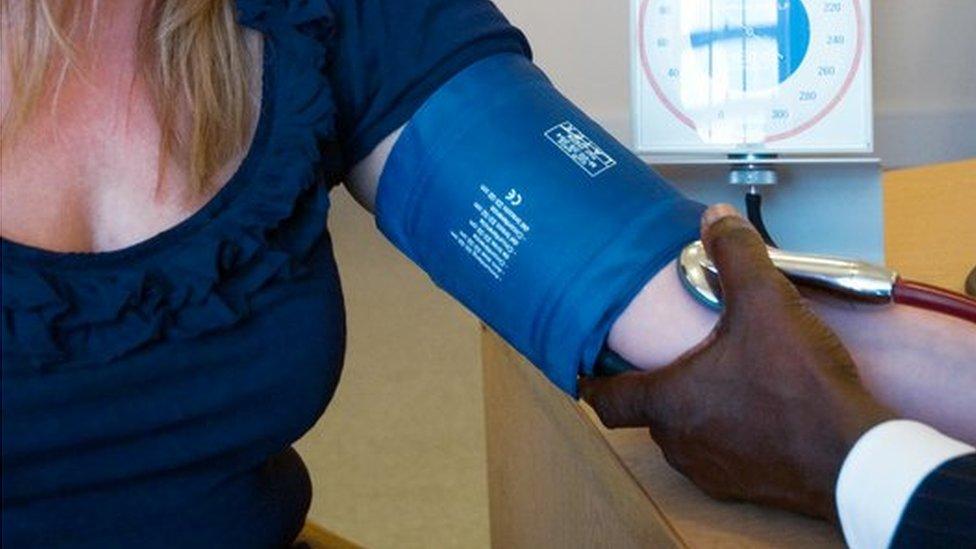 GP measuring blood pressure