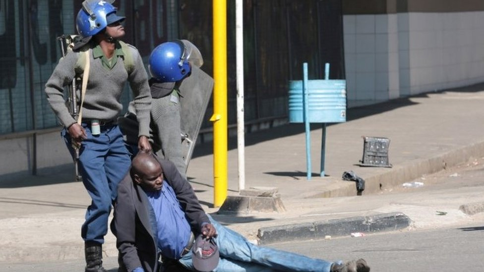 Police drag away protester as they disperse crowds in Harare - 16 August