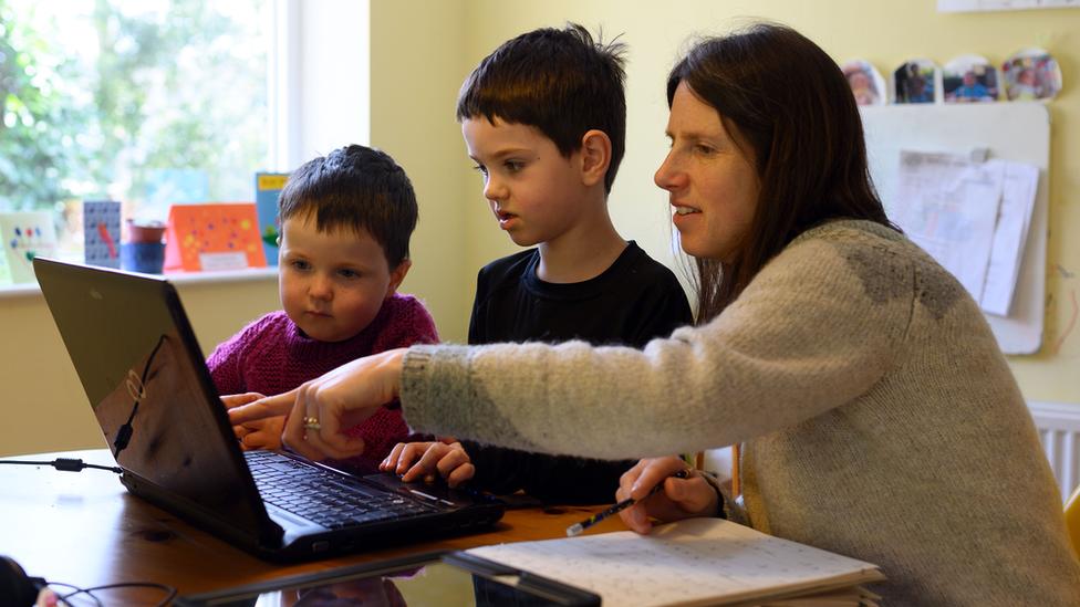 Madre e hijos frente a la computadora.