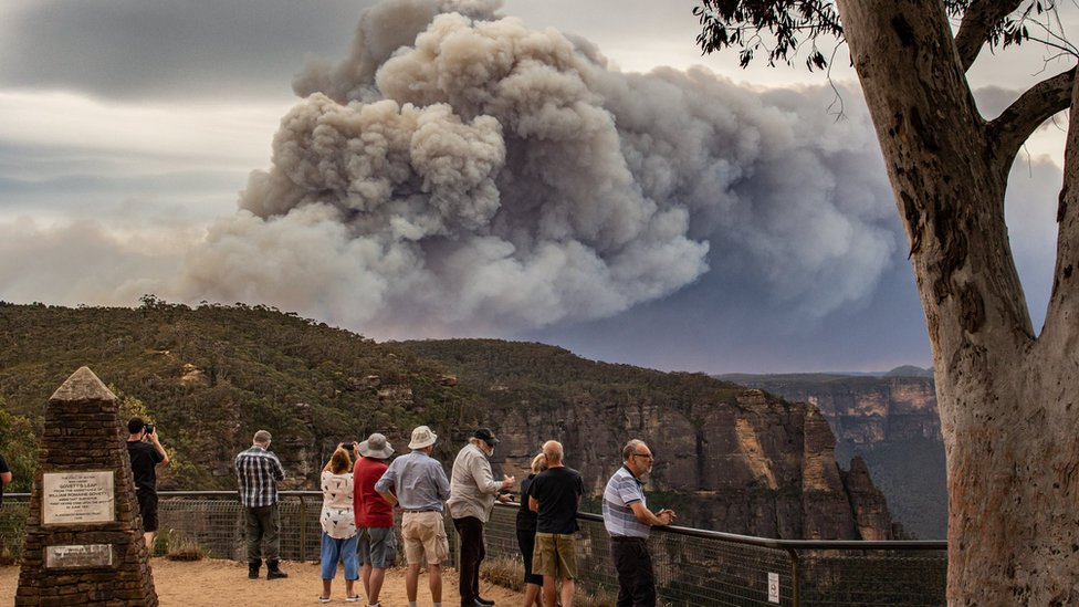 Tourists at a vantage point in the Blue Mountains look at huge smoke clouds from a bushfire