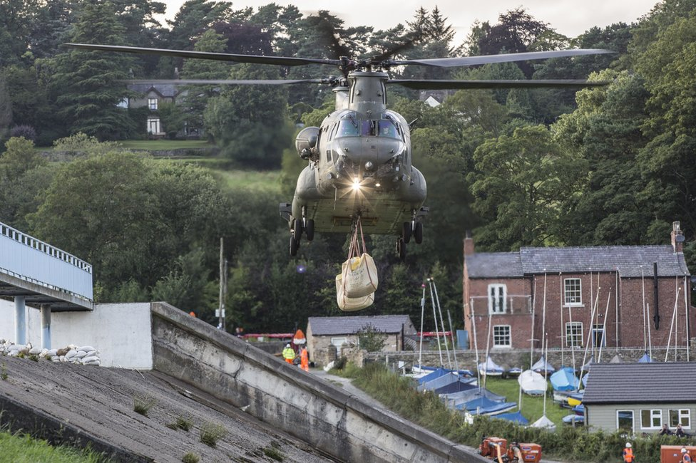 Chinook helicopter approaches with the load to drop on the dam in Whaley Bridge
