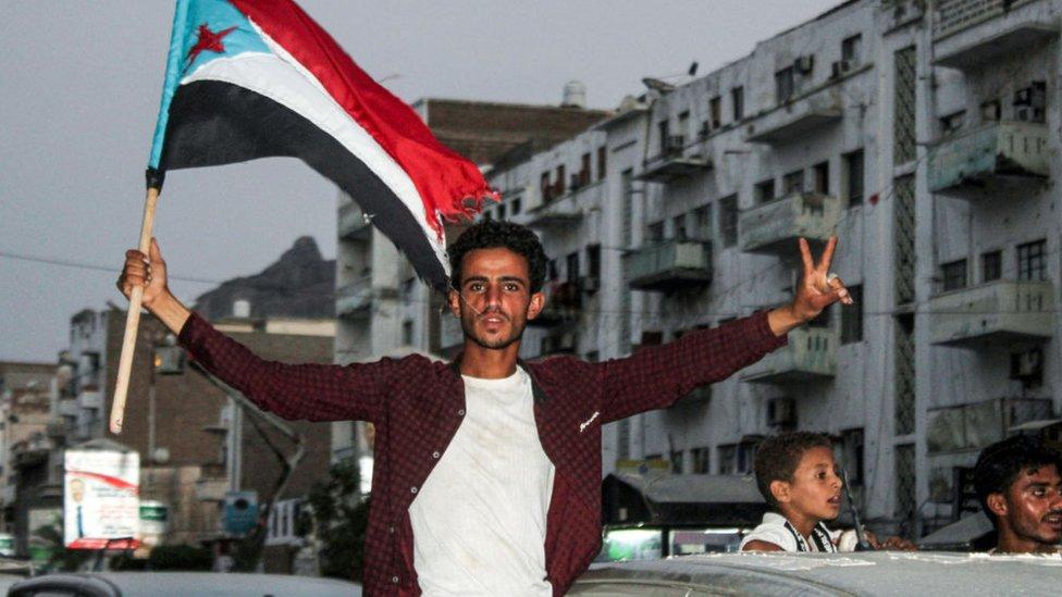 شاب يمني يرفع علم الجنوب
