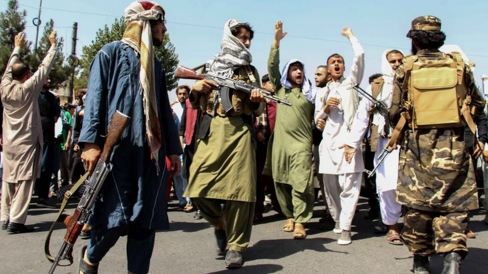 Armed Taliban fighters stand guard as protesters march in Kabul, Afghanistan. Photo: 7 September 2021