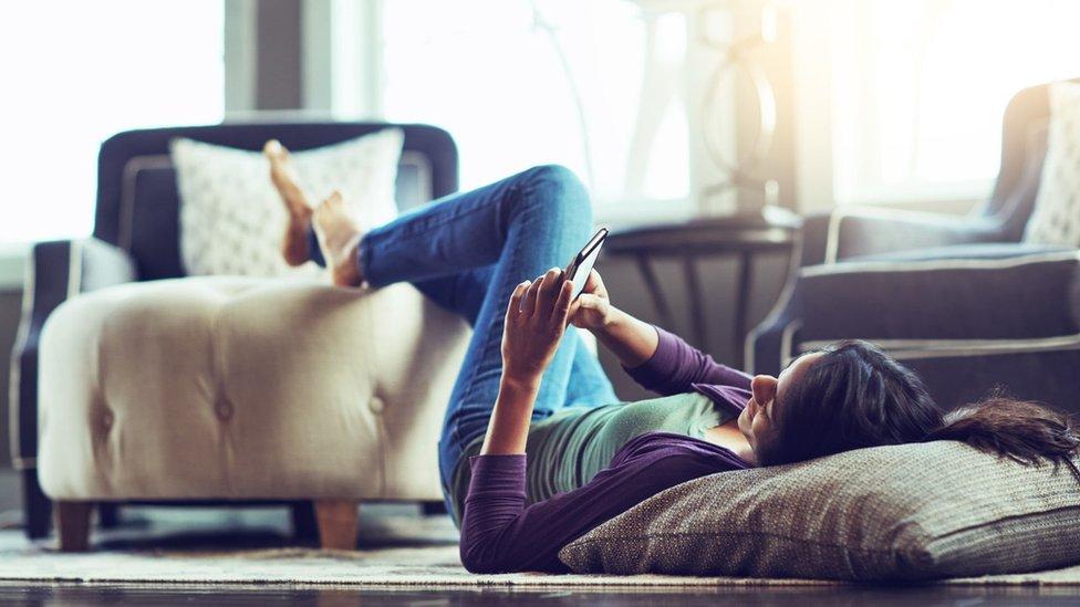 Una mujer mira su celular echada en el suelo.
