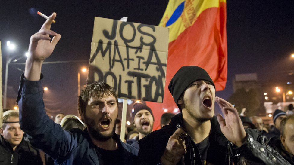"""Protesters hold a banner that reads: """"Down with the political mafia"""" at a rally in University Square, Bucharest, Romania. 4 Nov 2015"""