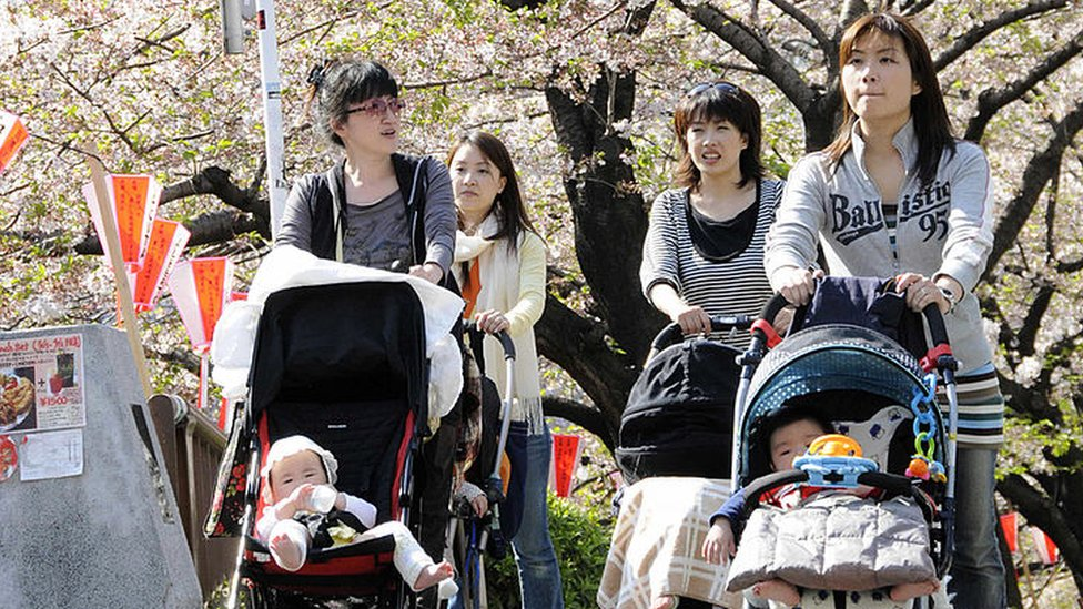 Young mothers push baby carriages s alongside a river in Tokyo on a sunny spring day