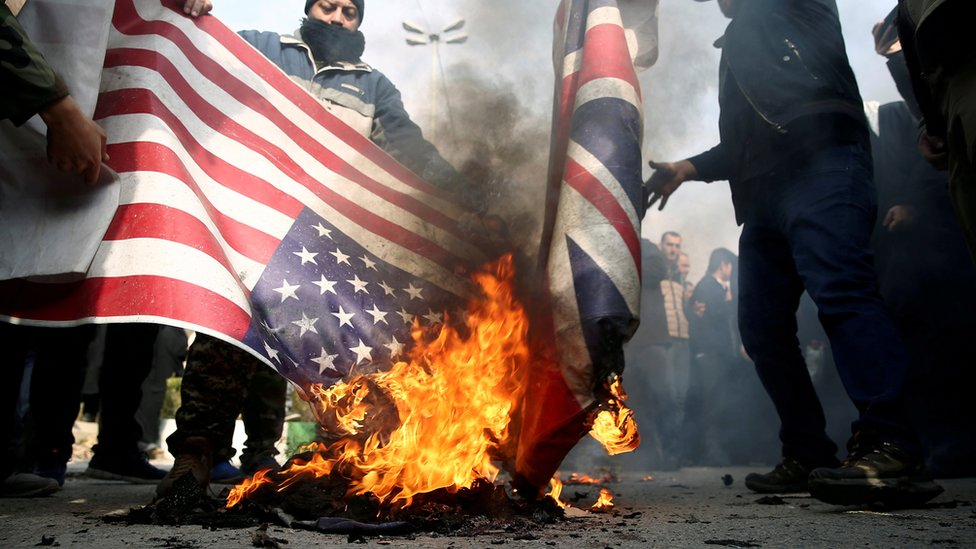 People burn US and British flags at a protest in Tehran, Iran, after the killing of Qasem Soleimani (4 January 2020)