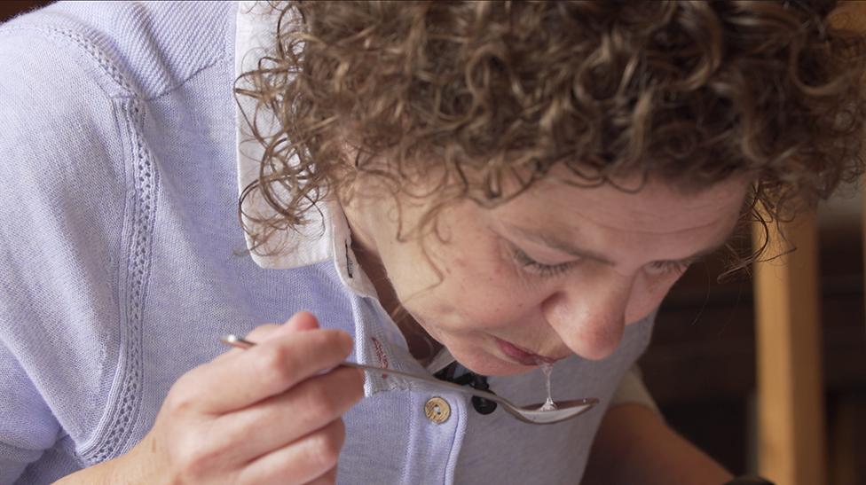 Mujer escupiendo en una cuchara