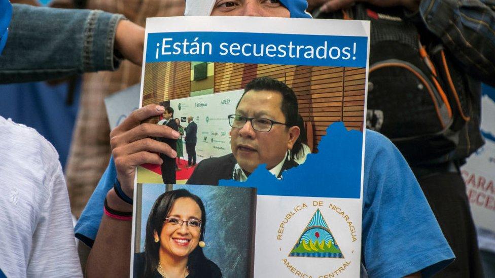 Manifestante con una foto de Miguel Mora y Lucía Pineda Ubau