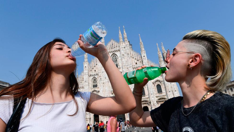 Dos chicas jóvenes toman agua en Milán