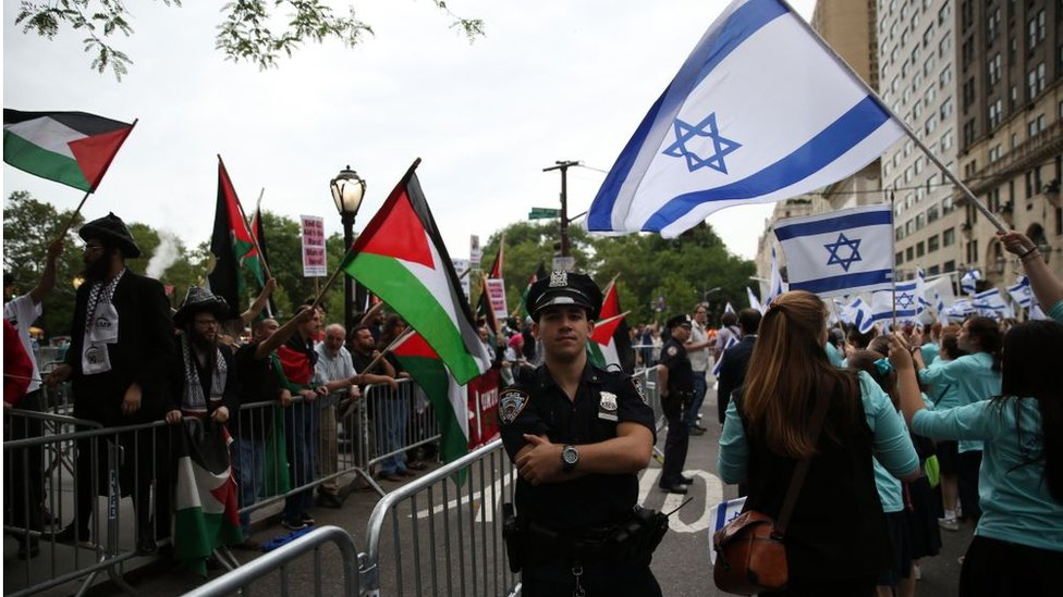 Pro-Israel and Pro-Palestine protesters waving respective country flags