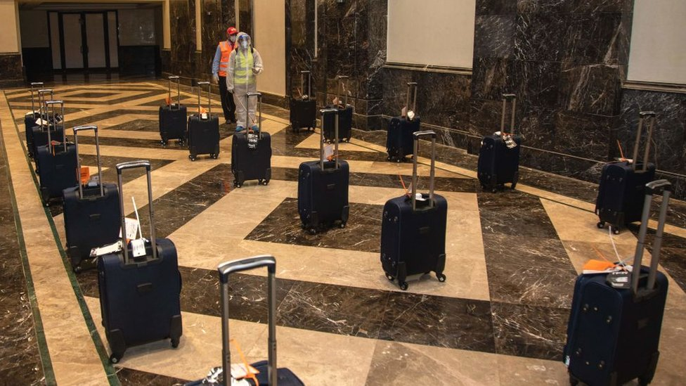 Workers sanitising pilgrims' luggage in a hotel lobby located near the Grand Mosque in Saudi Arabia's holy city of Mecca, during the annual hajj pilgrimage amid the coronavirus crisis