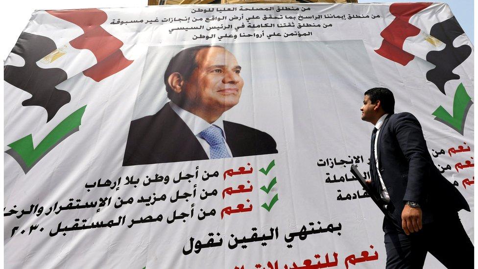 مصري يمر أمام لافتة لدعم السيسي
