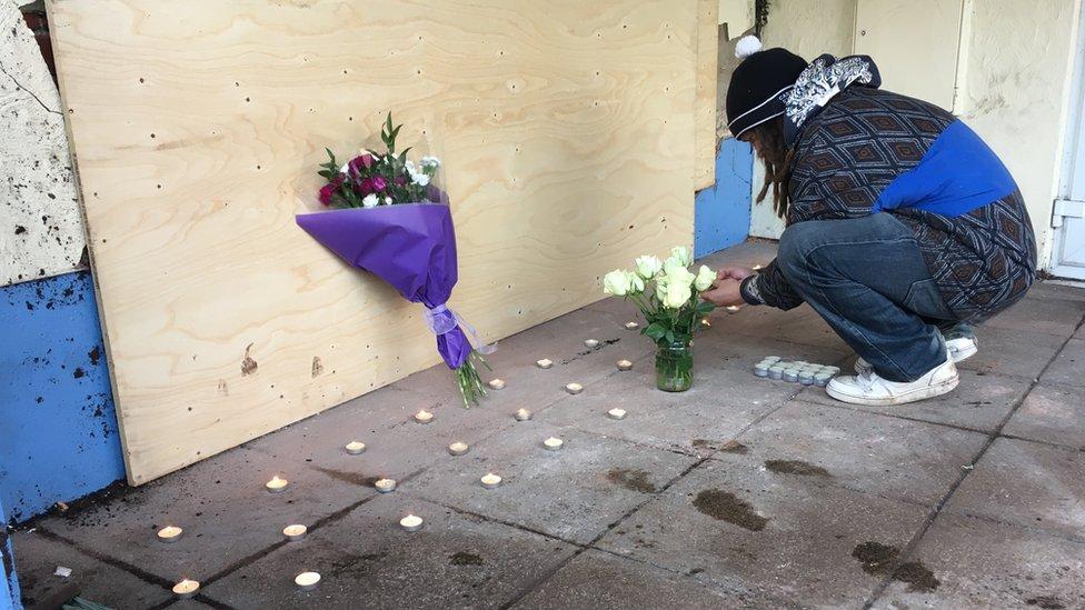 Friend Chris Hease lays flowers outside the Spinnaker Inn.