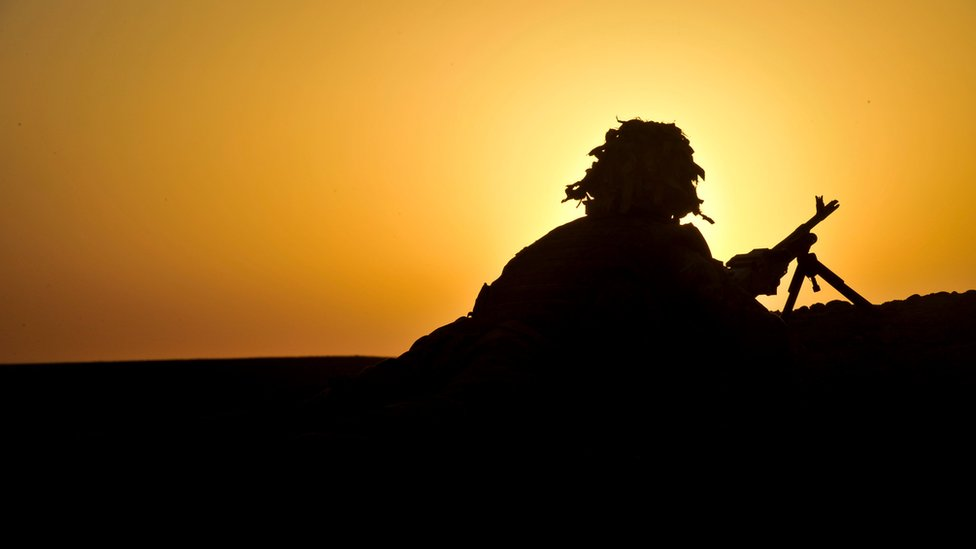 Silhouette of a soldier covering with a gun by a ridge