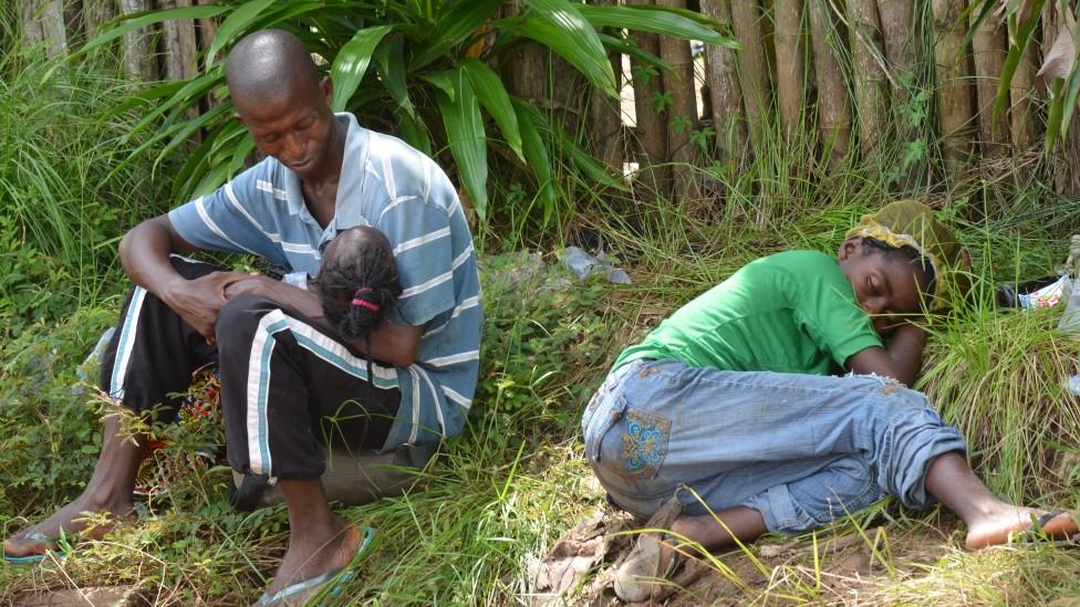Un padre con su niña pequeña en brazos y su mujer enferma recostada en el pasto aguardan para ser atendidos en una clínica