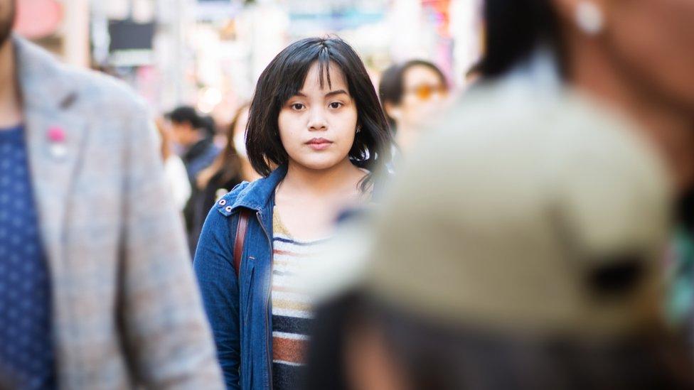 Mujer japonesa caminando sola entre la muchedumbre