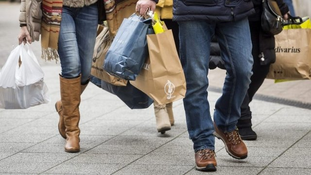 Christmas shoppers carry bags of goods