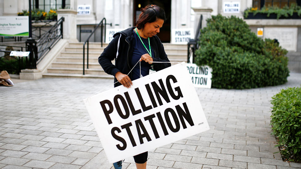 An electoral staff member places a sign outside a polling station for the European elections