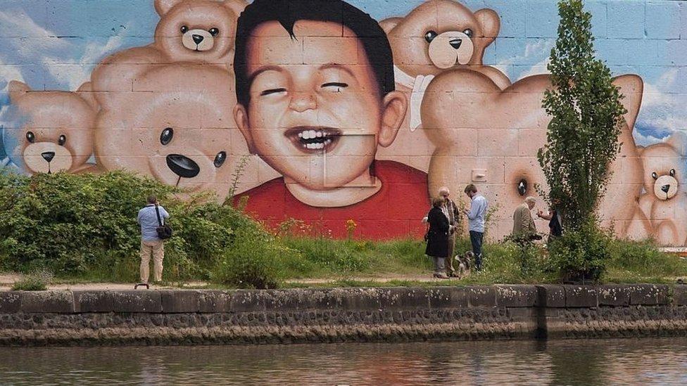 Mural de Aylan Kurdi pintado en una pared en Alemania.