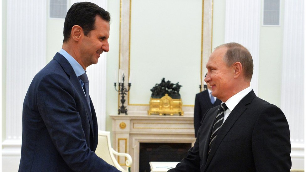 Bashar al-Assad shakes hands with Vladimir Putin in Moscow