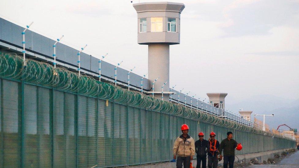 Trabajadores caminan por las inmediaciones de uno de los centros de educación en Sinkiang el 4 de septiembre de 2018.