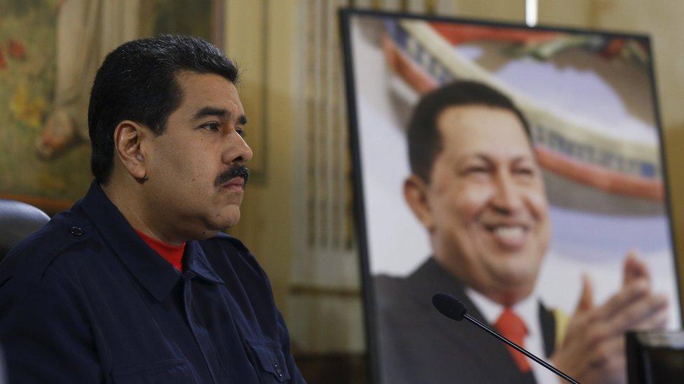 Venezuela's President Nicolas Maduro speaks next to a picture of late President Hugo Chavez