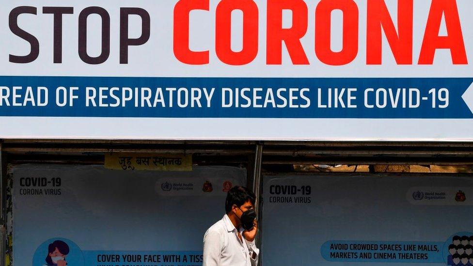 رجل في الهند يرتدي قناعا للوقاية من المرض