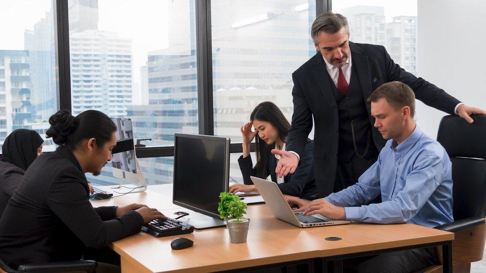 Jefe regañando a un empleado delante de sus compañeros.