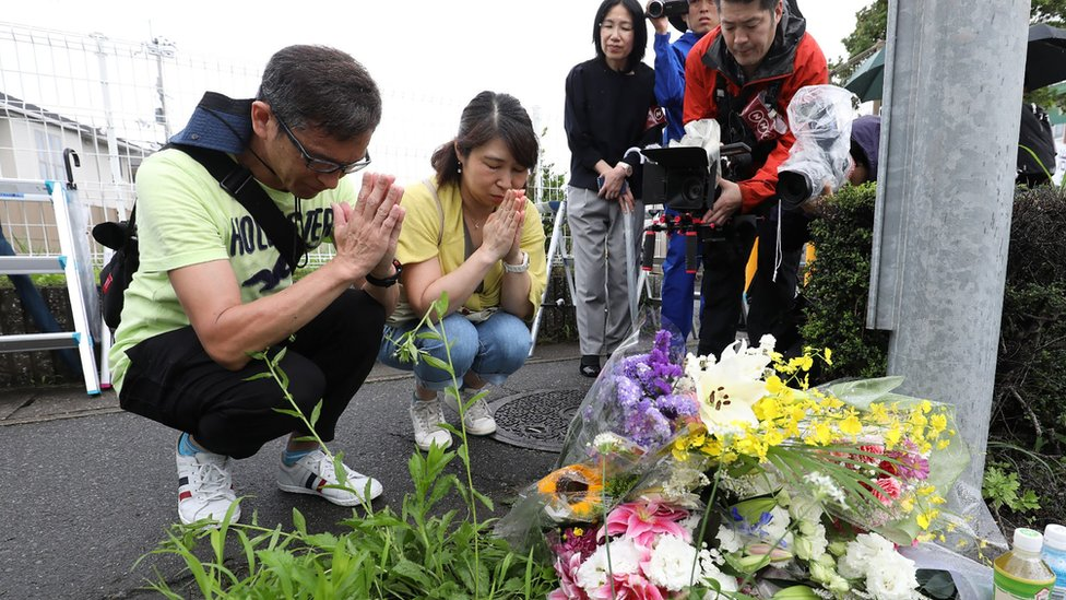 Residents pray for victims of a fire which hit the Kyoto Animation company studio