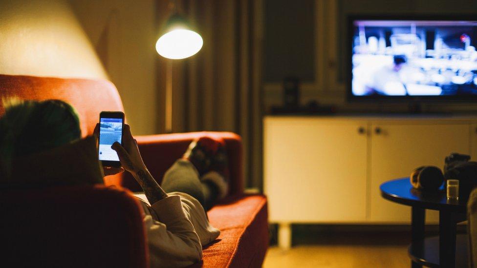 Mujer con celular y televisión.