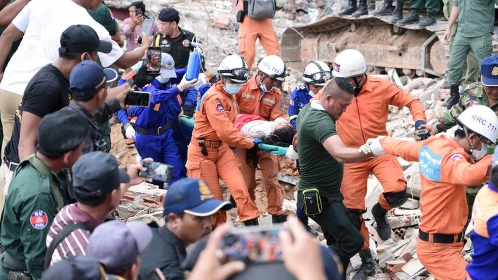 A rescue team carries a wounded worker from the collapsed building in Sihanoukville.