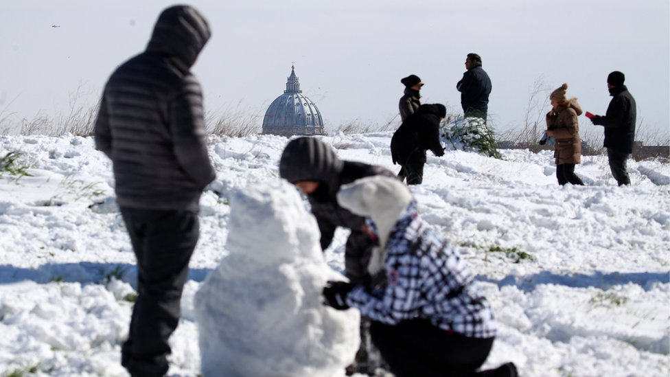 St Peter's Basilica is seen in the background as people enjoy the snow at the Circus Maximus in Rome