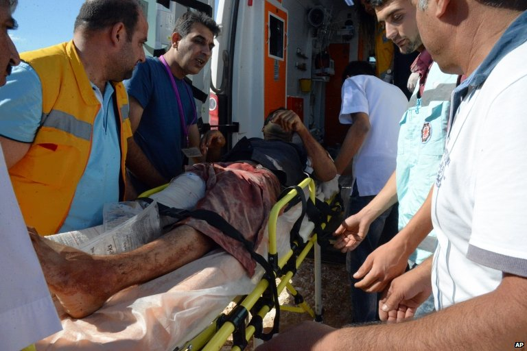Turkish medics carry a wounded person arrived from the Syrian town of Ayn al-Arab or Kobani following the attacks by IS militants, on the Turkish side of the border in Suruc, Turkey, on 25 June 2015