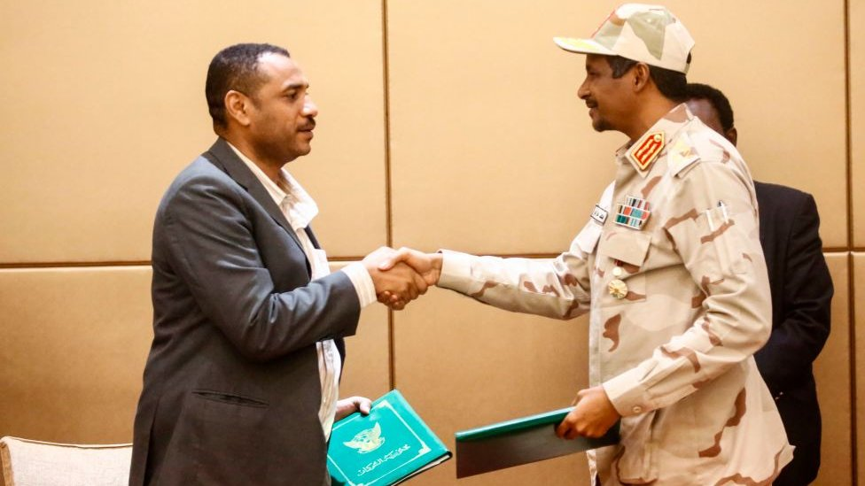 General Mohamed Hamdan Daglo (R), Sudan's deputy head of the Transitional Military Council, and protest leader Ahmed Rabie shake hands after signing the constitutional declaration